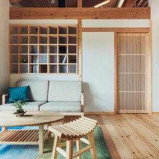 Exemple d'un petit salon asiatique ouvert avec une salle de réception, un mur blanc, un sol en bois clair, une cheminée standard, un manteau de cheminée en carrelage, un téléviseur fixé au mur, un sol beige, un plafond en poutres apparentes et du papier peint.