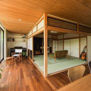 Diseño de salón con rincón musical abierto, asiático, con paredes blancas, suelo de madera en tonos medios y suelo verde