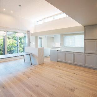 Esempio di un ampio soggiorno minimal aperto con sala formale, pareti grigie, pavimento in compensato, TV a parete, pavimento beige e soffitto in carta da parati
