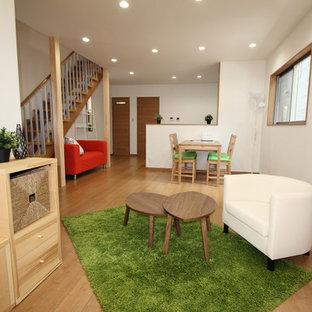Offenes Mid-Century Wohnzimmer mit weißer Wandfarbe, Sperrholzboden und beigem Boden in Sonstige