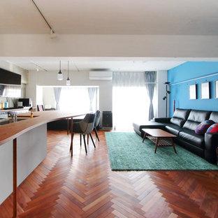 東京23区のアジアンスタイルのおしゃれなLDK (青い壁、濃色無垢フローリング、壁掛け型テレビ、茶色い床) の写真