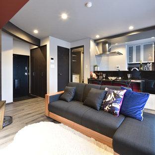 他の地域のモダンスタイルのおしゃれなLDK (黒い壁、塗装フローリング、据え置き型テレビ、グレーの床) の写真