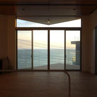 東京都下のビーチスタイルのおしゃれなLDK (白い壁、合板フローリング、据え置き型テレビ) の写真