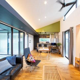 他の地域の中サイズのミッドセンチュリースタイルのおしゃれなLDK (緑の壁、無垢フローリング、壁掛け型テレビ、茶色い床) の写真