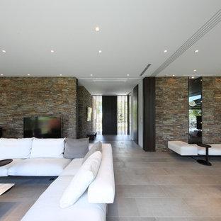 Foto di un soggiorno moderno aperto con TV autoportante, pavimento grigio e pareti multicolore