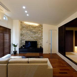 他の地域の中くらいのモダンスタイルのおしゃれなLDK (白い壁、合板フローリング、据え置き型テレビ、マルチカラーの床) の写真