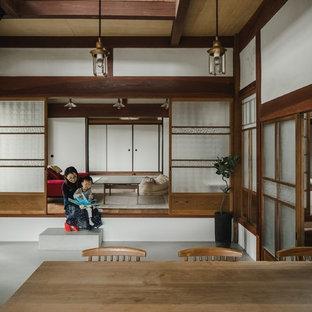 他の地域の巨大な和風のおしゃれな独立型リビング (白い壁、濃色無垢フローリング、壁掛け型テレビ、茶色い床) の写真