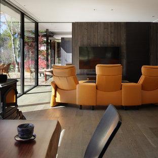 他の地域のコンテンポラリースタイルのおしゃれなリビング (グレーの壁、塗装フローリング、壁掛け型テレビ、グレーの床) の写真