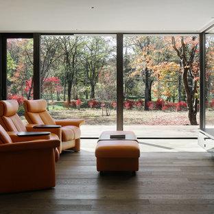 他の地域のコンテンポラリースタイルのおしゃれなLDK (茶色い壁、濃色無垢フローリング、薪ストーブ、石材の暖炉まわり、壁掛け型テレビ、茶色い床) の写真