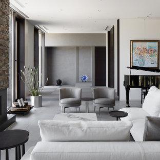 他の地域のコンテンポラリースタイルのおしゃれなリビング (マルチカラーの壁、コンクリートの床、グレーの床、標準型暖炉) の写真