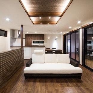 他の地域の中サイズのアジアンスタイルのおしゃれなリビング (白い壁、濃色無垢フローリング、据え置き型テレビ、茶色い床) の写真