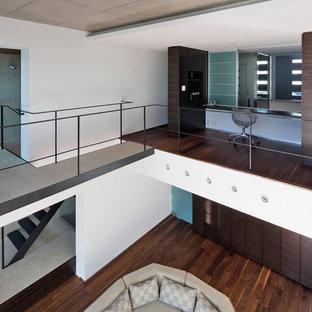Immagine di un soggiorno moderno aperto con pareti bianche, pavimento in compensato, nessun camino, TV autoportante e pavimento marrone