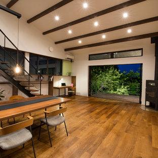 他の地域の広いモダンスタイルのおしゃれなLDK (白い壁、濃色無垢フローリング、コーナー設置型暖炉、金属の暖炉まわり、壁掛け型テレビ、茶色い床) の写真