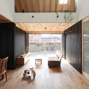 他の地域の中くらいのアジアンスタイルのおしゃれなLDK (黒い壁、無垢フローリング、壁掛け型テレビ、ベージュの床) の写真