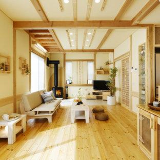 他の地域のアジアンスタイルのおしゃれなLDK (白い壁、淡色無垢フローリング、薪ストーブ、コーナー型テレビ、ベージュの床、表し梁) の写真