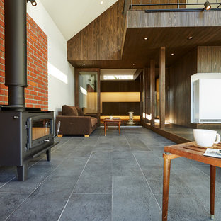 Ispirazione per un piccolo soggiorno minimalista aperto con sala formale, pareti arancioni, pavimento in gres porcellanato, stufa a legna, cornice del camino in mattoni, TV autoportante e pavimento nero
