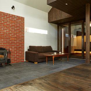 他の地域の小さいミッドセンチュリースタイルのおしゃれなLDK (薪ストーブ、レンガの暖炉まわり、オレンジの壁、磁器タイルの床、据え置き型テレビ、黒い床) の写真