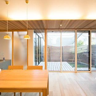 Foto de salón abierto, minimalista, pequeño, con paredes blancas, suelo de madera clara y televisor colgado en la pared