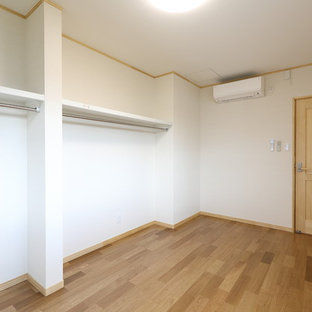 Design ideas for a large asian storage and wardrobe in Other with plywood floors and beige floor.