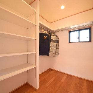 Cette photo montre un dressing et rangement moderne avec un placard à porte plane, des portes de placard en bois brun, un sol en contreplaqué, un sol marron et un plafond en papier peint.