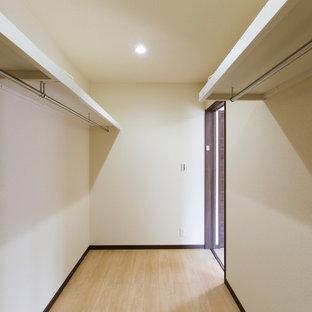 Foto di una cabina armadio per donna etnica con pavimento in compensato e pavimento beige
