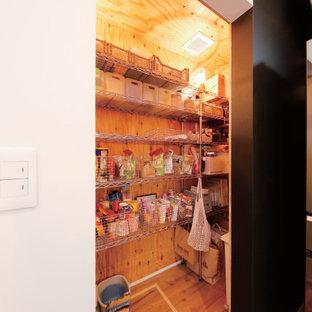 Immagine di una cabina armadio industriale di medie dimensioni con nessun'anta, ante grigie, pavimento in legno massello medio e pavimento marrone