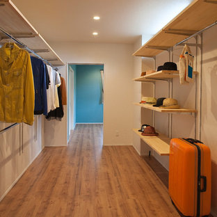 Foto di armadi e cabine armadio unisex moderni di medie dimensioni con pavimento in compensato, pavimento marrone e nessun'anta