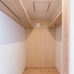 Ejemplo de armario vestidor unisex y papel pintado, pequeño, con suelo de madera en tonos medios, suelo marrón y papel pintado