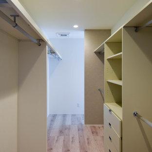 Diseño de armario vestidor unisex, contemporáneo, grande, con armarios abiertos, puertas de armario blancas, suelo de madera pintada y suelo blanco