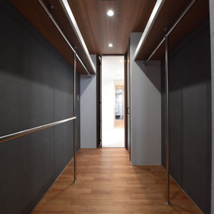 Foto på en funkis garderob, med plywoodgolv och brunt golv