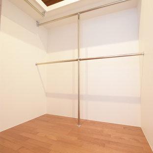 Immagine di una cabina armadio unisex moderna con pavimento in compensato e pavimento marrone
