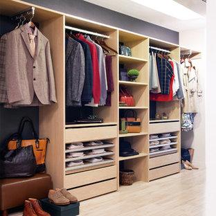 Modern inredning av ett walk-in-closet för könsneutrala, med öppna hyllor, skåp i ljust trä och ljust trägolv