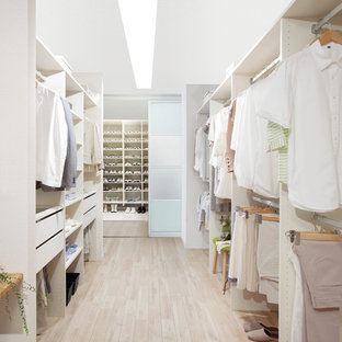 Design ideas for a large scandinavian gender-neutral walk-in wardrobe in Other with open cabinets, white cabinets, light hardwood floors and beige floor.