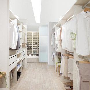 Diseño de armario vestidor unisex, escandinavo, grande, con armarios abiertos, puertas de armario blancas, suelo de madera clara y suelo beige