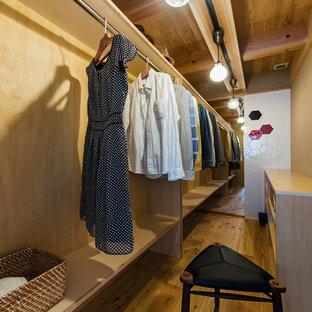 Réalisation d'un dressing asiatique neutre avec un placard sans porte, un sol en bois brun et un sol marron.
