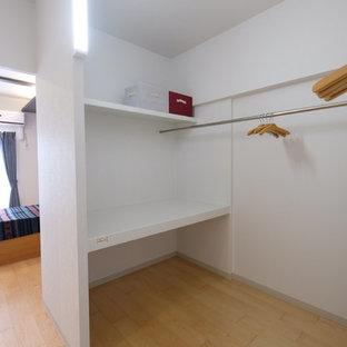 Cette photo montre un petit dressing moderne neutre avec un placard sans porte, des portes de placard blanches, un sol en contreplaqué et un sol beige.