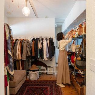 Modelo de vestidor unisex, asiático, con armarios abiertos, suelo de madera en tonos medios y suelo marrón