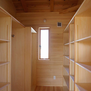 Large asian walk-in wardrobe in Other with light wood cabinets and light hardwood floors.