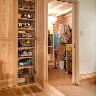 Immagine di una cabina armadio unisex etnica di medie dimensioni con ante in legno chiaro e parquet chiaro