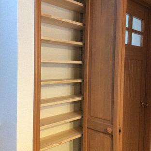 Imagen de armario y vestidor unisex y papel pintado, moderno, de tamaño medio, con armarios con paneles lisos, puertas de armario de madera oscura, suelo de madera pintada, suelo marrón y papel pintado