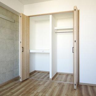 Foto di un armadio o armadio a muro stile rurale con ante in legno chiaro, pavimento in compensato e pavimento marrone