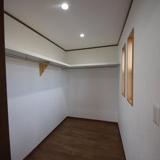 Immagine di una grande cabina armadio minimalista con pavimento in legno verniciato e pavimento marrone