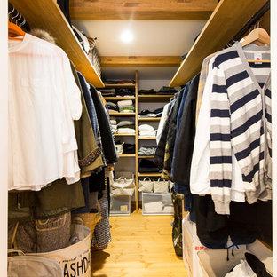 Diseño de armario vestidor urbano con suelo de madera en tonos medios, armarios abiertos y suelo marrón