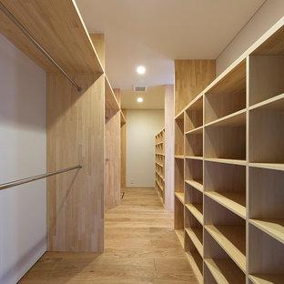 Cette photo montre un petit dressing moderne neutre avec un placard sans porte, des portes de placard en bois clair, un sol en contreplaqué et un sol beige.