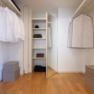 Ejemplo de armario vestidor moderno con armarios con paneles lisos, suelo de madera en tonos medios y suelo marrón