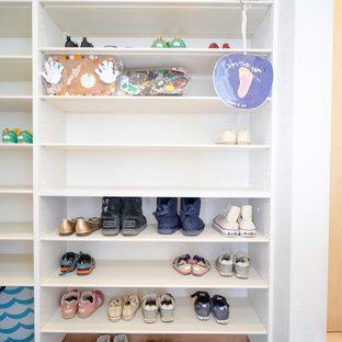 Inspiration för mellanstora moderna walk-in-closets för könsneutrala, med öppna hyllor, vita skåp, klinkergolv i terrakotta och beiget golv