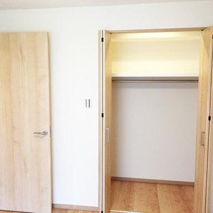 Ispirazione per un armadio o armadio a muro etnico con pavimento in legno massello medio