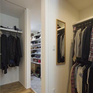 Imagen de armario vestidor unisex y papel pintado, moderno, de tamaño medio, con armarios abiertos, puertas de armario blancas, suelo de madera clara, suelo marrón y papel pintado