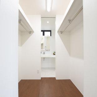 Aménagement d'un dressing moderne neutre avec un sol en contreplaqué et un sol marron.