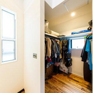 Imagen de armario vestidor minimalista con suelo de madera en tonos medios y suelo rosa